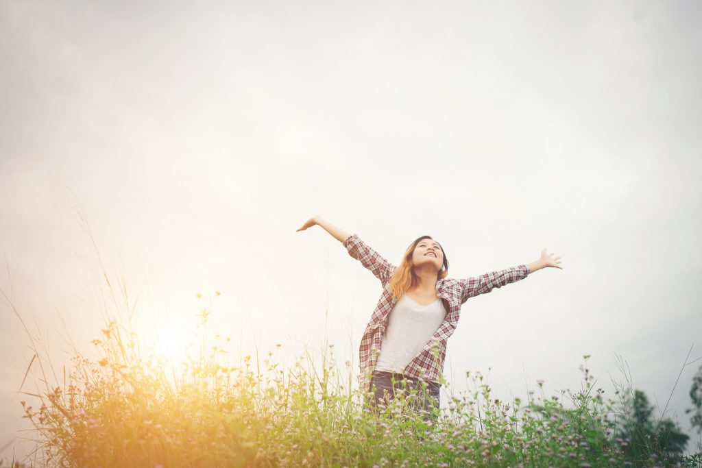 Trauma and the Body: Young beautiful hipster woman in a flower field at sunset. Freed