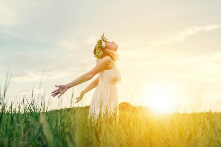 Lady with arms open facing the sun